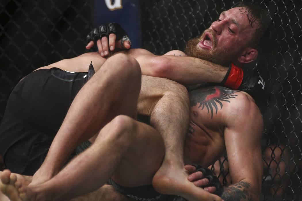Khabib Nurmagomedov mantiene a Conor McGregor en la lona durante su pelea por el título en el UFC 229 en el T-Mobile Arena en Las Vegas, el sábado 6 de octubre de 2018. Foto Chase Stevens / Las ...