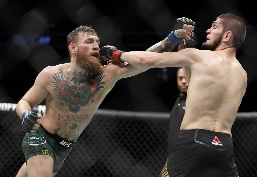 Conor McGregor, izquierda, y Khabib Nurmagomedov lanzan golpes durante una pelea de artes marciales mixtas de título ligero en UFC 229 en Las Vegas, sábado 6 de octubre de 2018. (Foto AP / John ...
