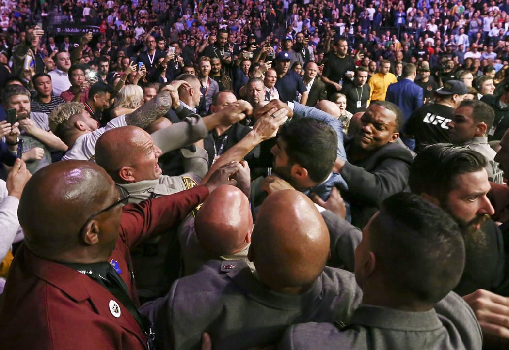 La policía y el equipo de seguridad de Las Vegas intentan detener las peleas que se desataron después de que Khabib Nurmagomedov saltara del octágono luego de su victoria sobre Conor McGregor e ...