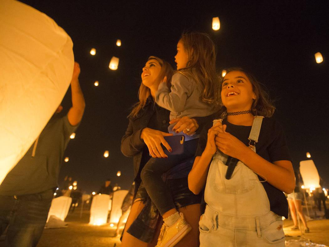 Jessica, June y Jade Laos observan cómo sus linternas vuelan hacia el cielo durante el Festival RiSE Lantern en el Jean Dry Lake Bed el viernes 5 de octubre de 2018 en Jean, Nevada. Benjamin Hage ...
