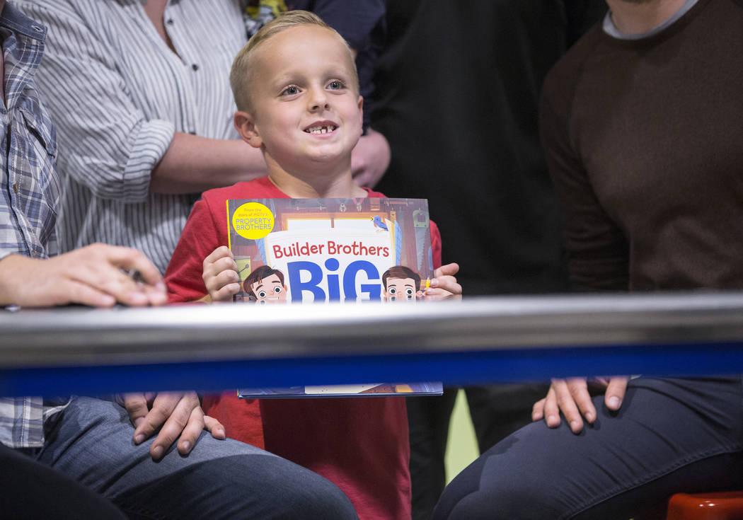 """Colton Shrivel, de 6 años, sonríe a lo grande por su foto con Jonathan y Drew Scott de """"Property Brothers"""" durante una firma de libros en el Discovery Children's Museum el lunes 8 de octubre de ..."""