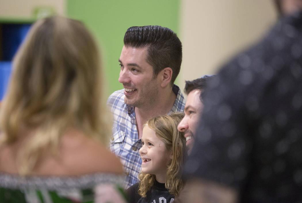 """Jonathan, en medio, y Drew Scott, de """"Property Brothers"""", se toman una foto con Dominic Kleckner, de 7 años, durante una firma de libros en el Discovery Children's Museum el lunes 8 de octubre de ..."""
