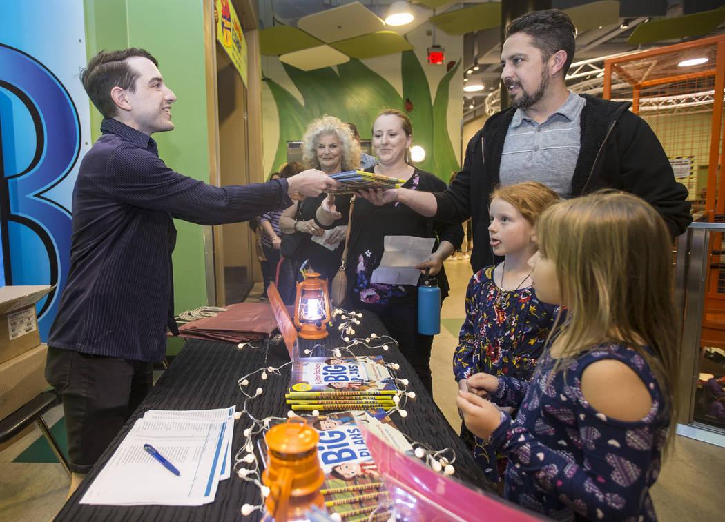 """Drew Cohen, a la izquierda, entrega una copia del nuevo libro para niños de Jonathan y Drew Scott """"Builder Brothers Big Plans"""" a Sia Mozaffarimehr durante una firma de libros en el Discovery Chil ..."""