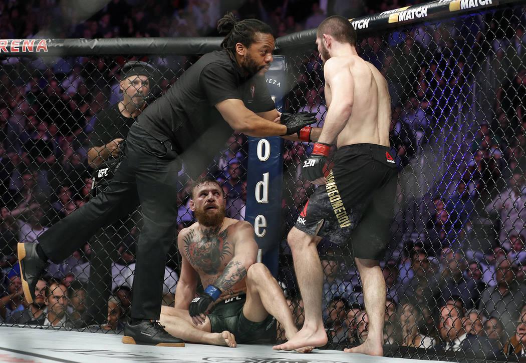 Khabib Nurmagomedov, a la derecha, es retenido por el árbitro Herb Dean después de pelear con Conor McGregor, en el fondo, durante un combate de artes marciales mixtas de título ligero en UFC 2 ...