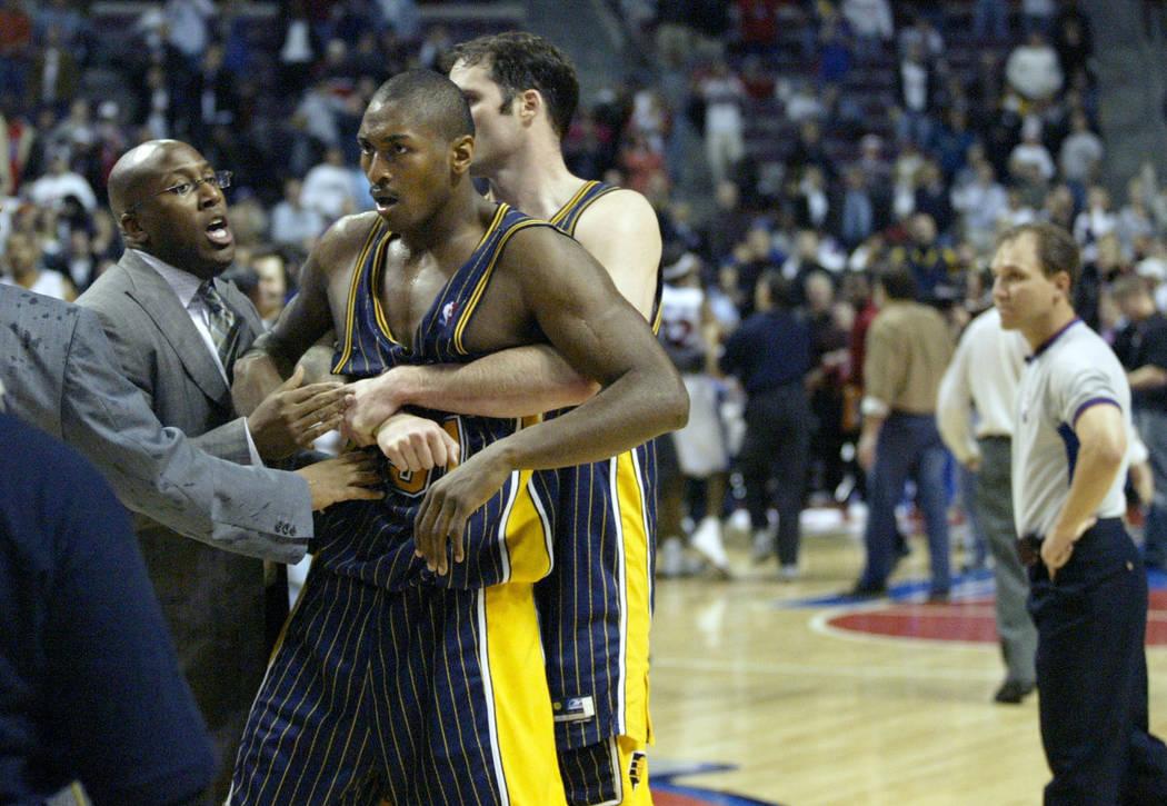 ARCHIVO: en esta foto de archivo del 19 de noviembre de 2004, Ron Artest de Indiana Pacers es restringido antes de ser escoltado fuera de la cancha luego de una pelea contra los Detroit Pistons y ...