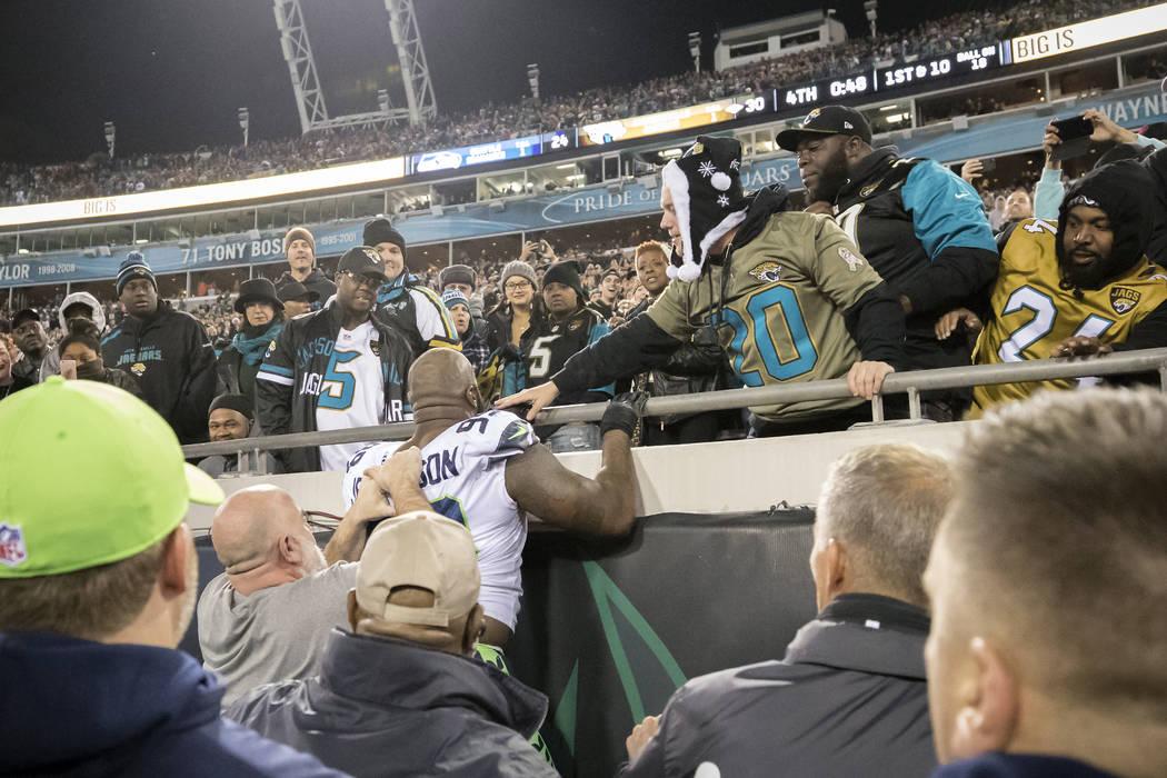 El tackle defensivo de los Seattle Seahawks, Quinton Jefferson, centro, trata de escalar las gradas después de que los fans de los Jacksonville Jaguars le lanzaran objetos al final de un partido ...