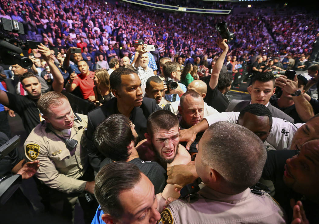 Khabib Nurmagomedov es retenido fuera de la jaula después de vencer a Conor McGregor en una pelea de artes marciales mixtas de título ligero en UFC 229 en Las Vegas, sábado 6 de octubre de 2018 ...