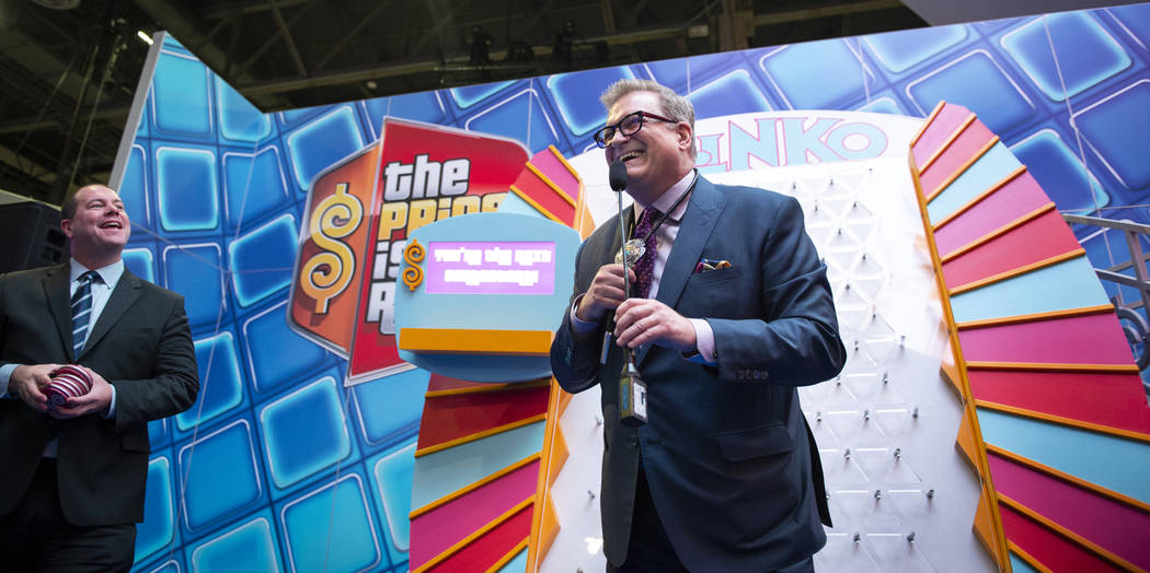 Dallas Orchard, Director de Producto de IGT, izquierda, observa mientras el ícono de entretenimiento y famoso presentador de juegos Drew Carey lidera el estreno mundial de tres juegos de tragamon ...