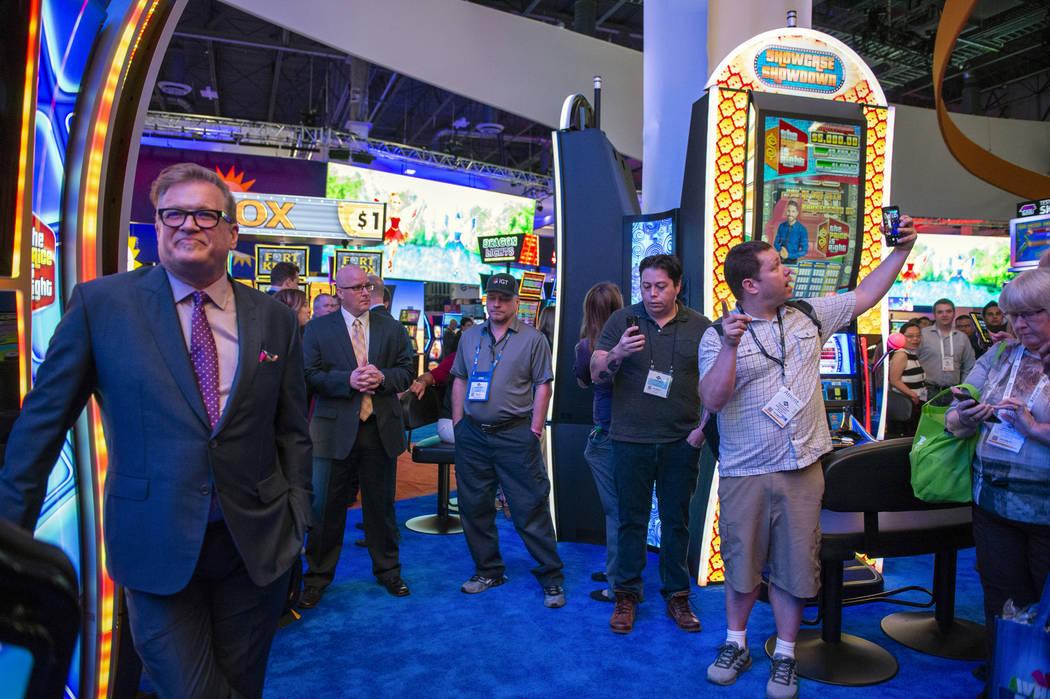 El famoso presentador de juegos, Drew Carey, se encuentra al lado de uno de los juegos de tragamonedas IGT Price is Right, mientras que un fanático se toma una selfie con el ícono de entretenimi ...
