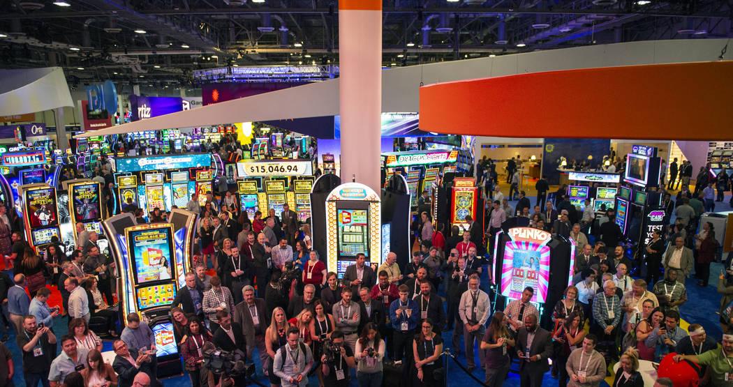 Una multitud se reúne en el stand de IGT mientras el presentador de juegos Drew Carey lidera el estreno mundial de tres juegos de tragamonedas IGT The Price is Right en la 18a edición de la Glob ...