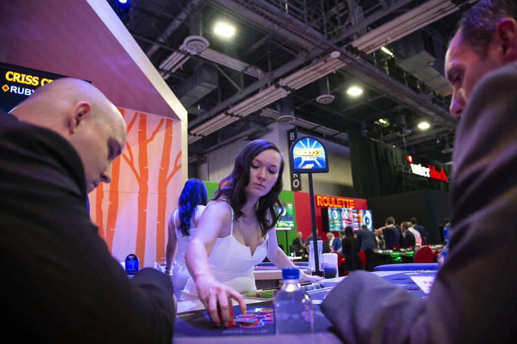 Olivia Paiz, de Las Vegas, reparte fichas de póquer en la mesa de AGS Criss Cross Poker en la 18ª Exposición Global de Juegos en el Sands Expo and Convention Center en Las Vegas, el miércoles ...