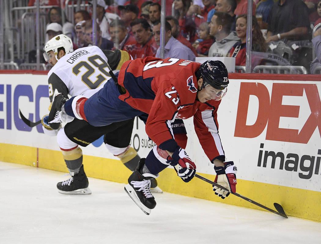 El alero derecho de los Washington Capitals, Dmitrij Jaskin (23), cae al hielo junto al alero izquierdo de los Golden Knights de Las Vegas, William Carrier (28) durante el primer período de un ju ...