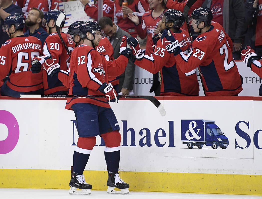 El centro de Washington Capitals, Evgeny Kuznetsov (92), de Rusia, celebra su gol con sus compañeros de equipo en el banco durante el primer período de un juego de hockey de la NHL contra Vegas ...
