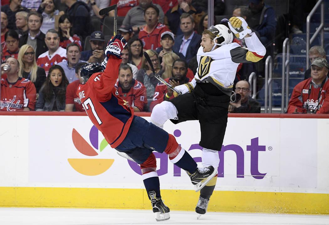 El alero derecho de los Washington Capitals, T.J. Oshie, a la izquierda, choca con Jon Merrill, defensor de los Golden Knights de Las Vegas, durante el segundo período de un juego de hockey de la ...