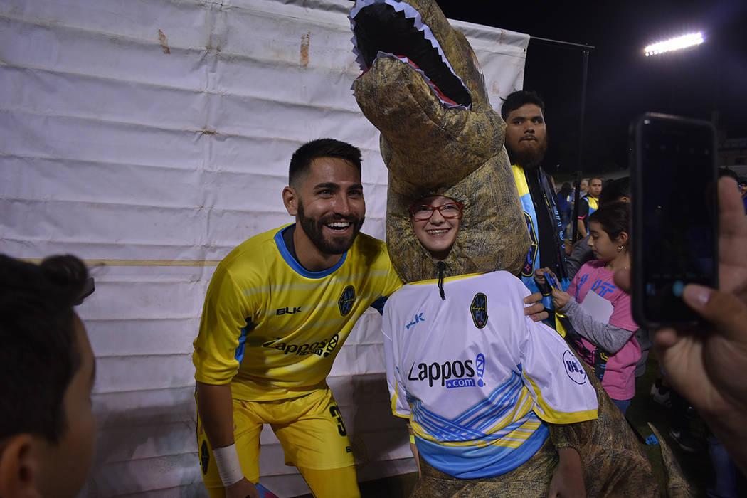 El portero de Lights FC, Thomas Olsen (30) convive con una niña aficionada que se disfrazó como dinosaurio. Miércoles 10 de octubre de 2018 en Cashman Field. Foto Anthony Avellaneda / El Tiempo.