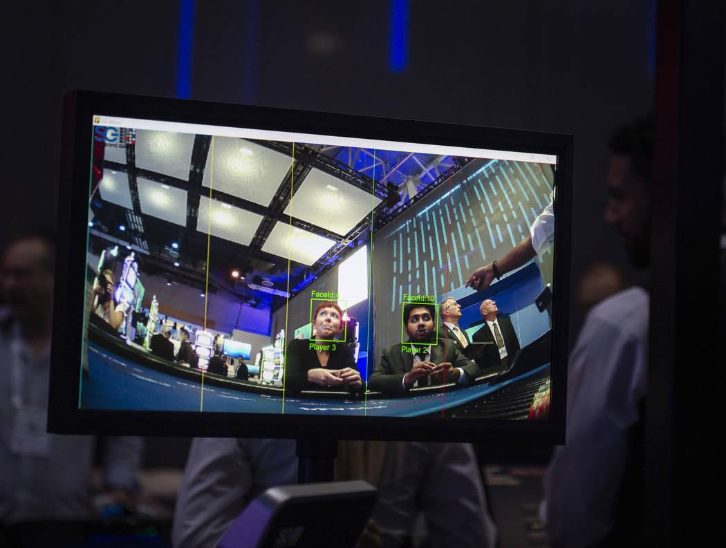 Los asistentes juegan al póquer que utiliza una visión por computadora que ofrece clasificaciones en tiempo real y análisis de juegos de mesa en el stand de Scientific Games en la 18º Exposici ...