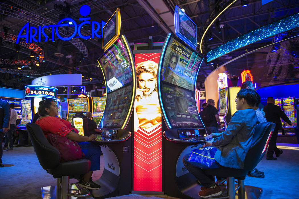 Los asistentes prueban las máquinas tragamonedas con el tema de Madonna que cuentan con una pantalla curva en el stand de Aristocrat en la 18a Exposición Global de Juegos Anual en el Sands Expo ...