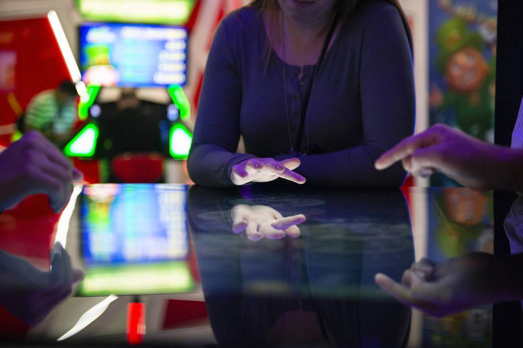 Los asistentes juegan un juego de mesa con el tema de Deal or No Deal que utiliza tecnología de pantalla táctil en el stand de Gamblit en la 18º Global Global Expo en Sands Expo and Convention ...