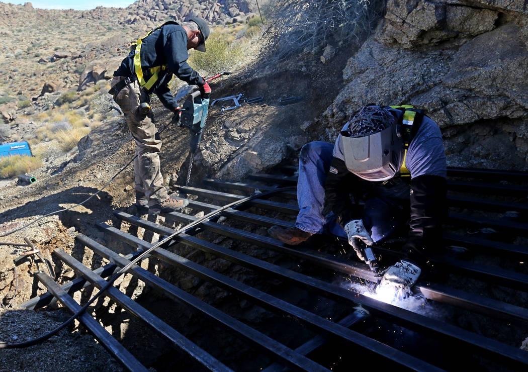 Los contratistas estatales, Brian Breiter, a la izquierda, y James Ryan aseguraron el acero a través de la apertura de una mina abandonada en el Monumento Nacional Gold Butte, el lunes 8 de octub ...
