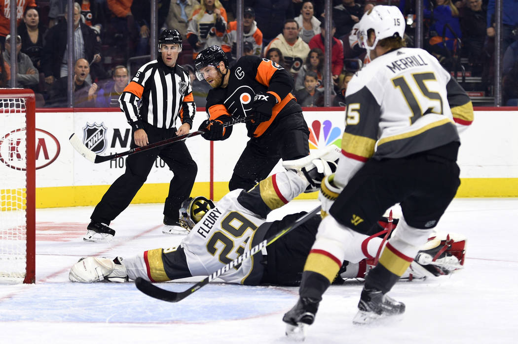Claude Giroux, de Philadelphia Flyers, en el centro, mira el puck cuando el portero Marc-André Fleury (29) de los Golden Knights, hace un rescate de guante durante el segundo período de un juego ...