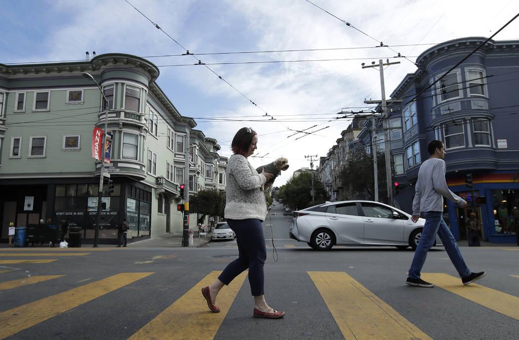 Christin Evans, propietaria de The Booksmith, lleva a su perro Joey Pistachio mientras cruza Ashbury Street por Haight Street en San Francisco, el 1 de octubre de 2018. (Foto AP / Jeff Chiu)