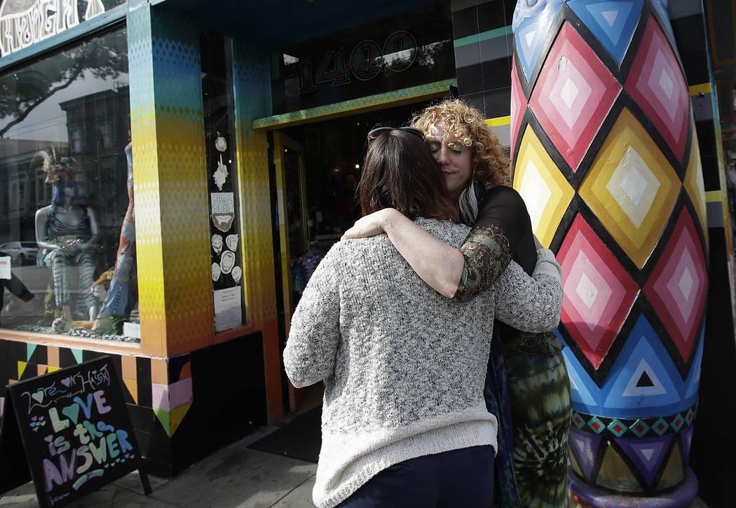 Sunshine Powers, dueño de la tienda Love on Haight, a la derecha, abraza a Christin Evans, dueña de The Booksmith, afuera de la tienda de Powers en San Francisco, el 1 de octubre de 2018. (AP Ph ...