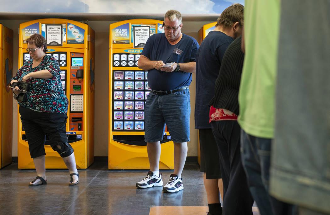 Rob Foos de Ohio rasca sus boletos de lotería recientemente comprados para ganancias potenciales en Primm Valley Lotto Store en Primm, el lunes 15 de octubre de 2018. (Caroline Brehman / Las Vega ...