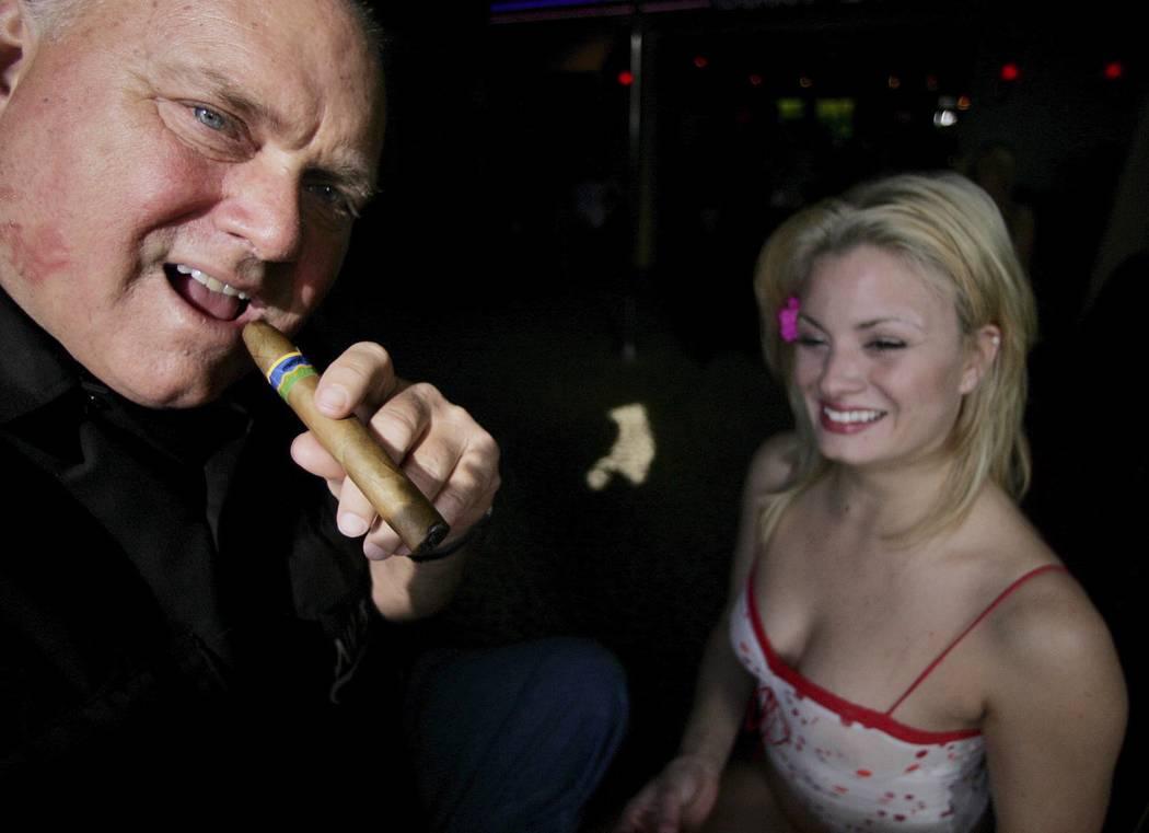 El propietario de Moonlite BunnyRanch Dennis Hof fuma un cigarro en la entrada de su burdel, el jueves 7 de abril de 2005, en Mound House, Nevada (Foto AP / Brad Horn)