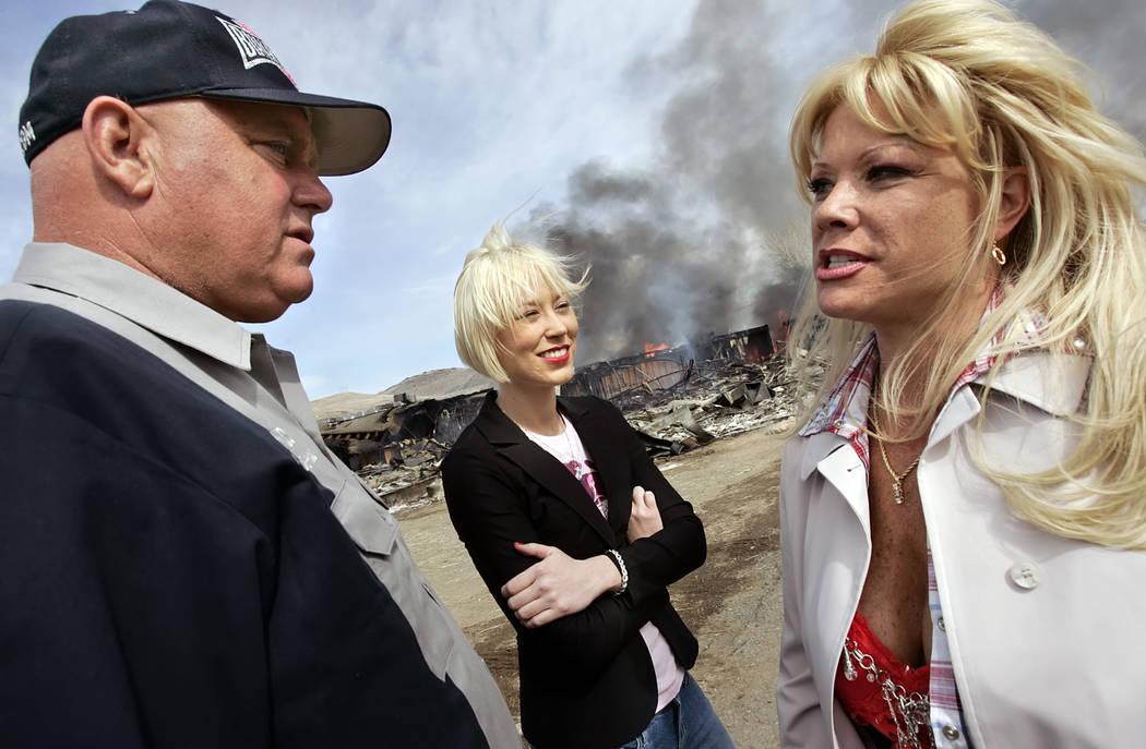 """El dueño del burdel Moonlite Bunny Ranch, Dennis Hof, a la izquierda, habla con dos de sus empleadas, Brooke Taylor, centro, y una mujer que se identificó como """"Air Force Amy"""" mientras visitan l ..."""