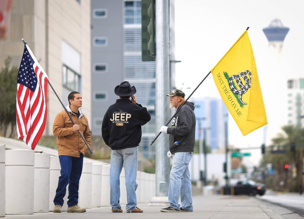 Joshua Martínez, a la izquierda, Greg Whalen, centro, y Michael Elliot, se ubican fuera del palacio de justicia Lloyd D. George para demostrar su apoyo a la familia Bundy en Las Vegas el viernes ...