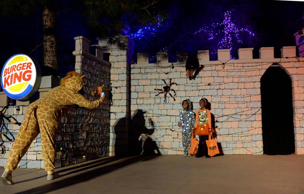 Serena Garrett, izquierda, toma una fotografía de Anahi Crockett, de 5 años, y Addison Reed, de 5, en el evento HallOVeen en el Bosque Mágico de Opportunity Village en Las Vegas, domingo 21 de ...