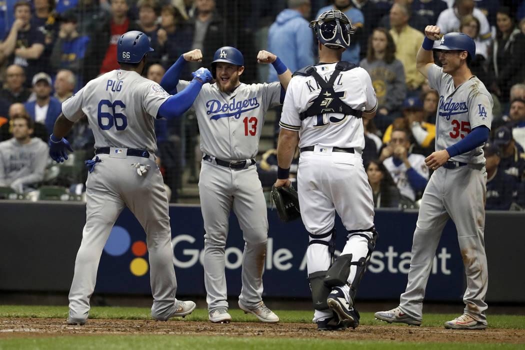 Yasiel Puig (66) de los Dodgers de Los Ángeles celebra con Max Muncy (13) y Cody Bellinger (35) luego de batear un jonrón de tres carreras durante la sexta entrada del Juego 7 del juego de béis ...