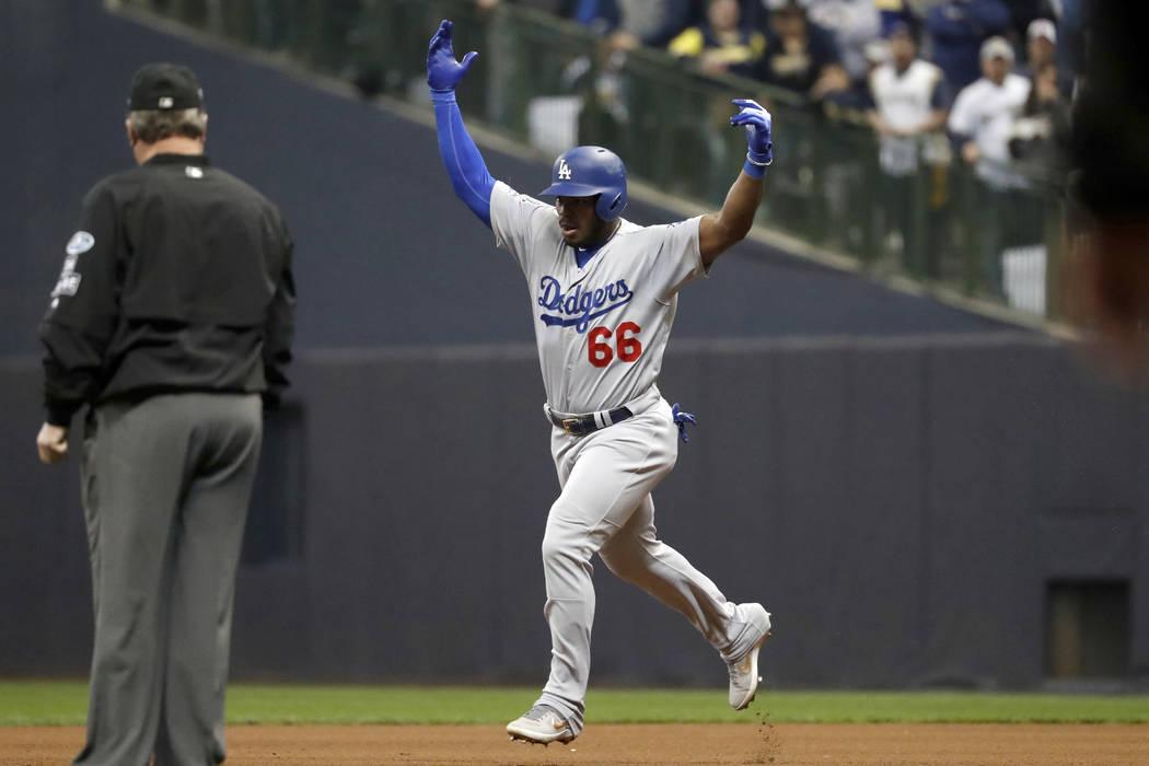 Yasiel Puig (66), de los Dodgers de Los Ángeles, celebra cuando corre las bases luego de batear un jonrón de tres carreras durante la sexta entrada del Juego 7 del juego de béisbol de la Serie ...