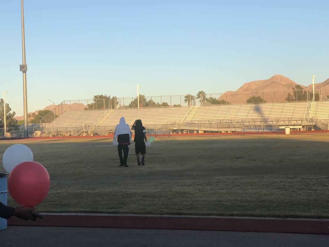 Los hijos de Susan Nash, De'Angelo y De'Andre Nash, a la derecha, caminan hacia el centro del campo de fútbol de Desert Pines High School, donde se pintó un corazón con las iniciales de su madr ...