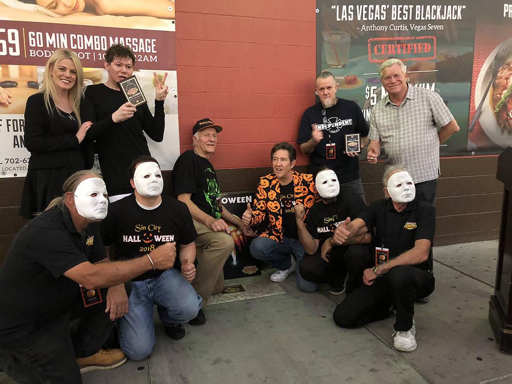 """George P. Wilbur y Paul Casey (al centro), entre el grupo que posó junto a la placa dedicada al productor John Carpenter, """"Maestro del Horror"""". Sábado 27 octubre de 2018, en la Fremont East. ..."""