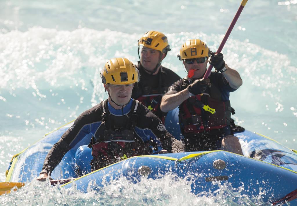 """El bombero Tim McKeever Junior, desde la izquierda, el """"bombero"""" víctima Ian Bradley y el ingeniero Kevin Flynn, devuelven la balsa a la costa durante el entrenamiento de rescate acuático en la ..."""