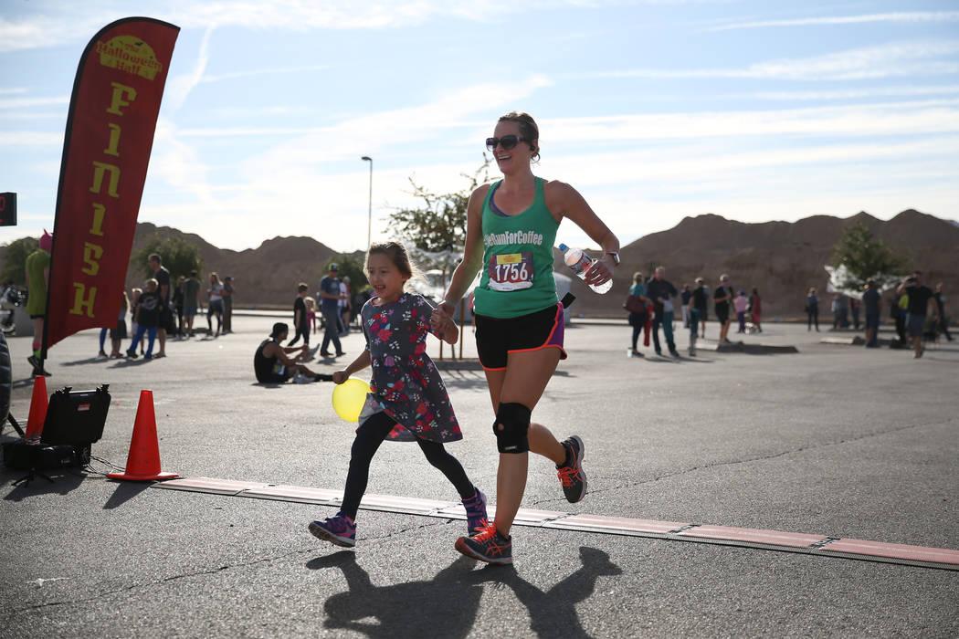 Shae Deschutter de Henderson corre hasta la línea de meta con su hija Brighton, de 5 años, durante Halloween Half en el hotel-casino Fiesta Henderson en Las Vegas, el sábado 27 de octubre de 20 ...