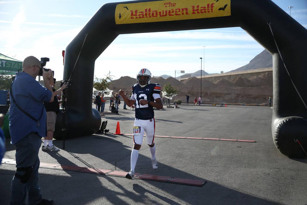 Paul Naylor, de 33 años, de Las Vegas, cruza la línea de meta en su récord Guinness World Records para obtener el medio maratón más veloz portando equipo de fútbol, durante Halloween Half en ...