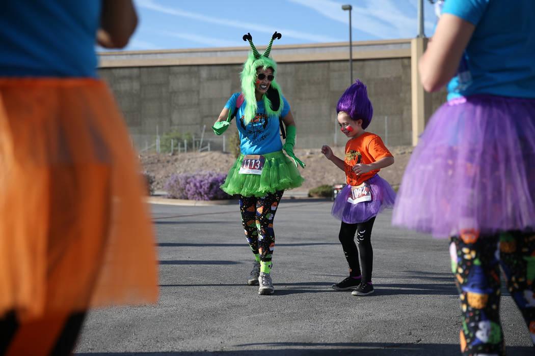 Tracey Fabre, a la izquierda, con su sobrina Ashely Del Rial, de 6 años, baila al ritmo de la música antes de que comience Halloween 5K en el hotel-casino Fiesta Henderson en Las Vegas, el sába ...