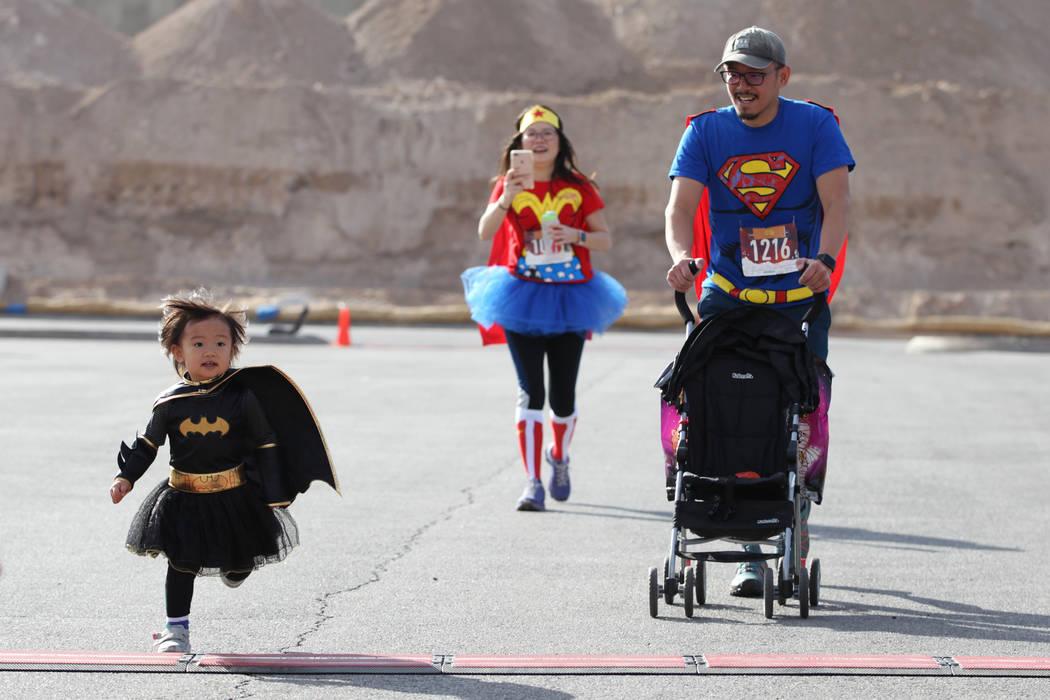 Maya Lim, 2, de izquierda a derecha, llega hasta el final con sus padres Olivia Chao y Seng Lim, durante la carrera de Halloween 5K en el hotel-casino Fiesta Henderson en Las Vegas, el sábado 27 ...