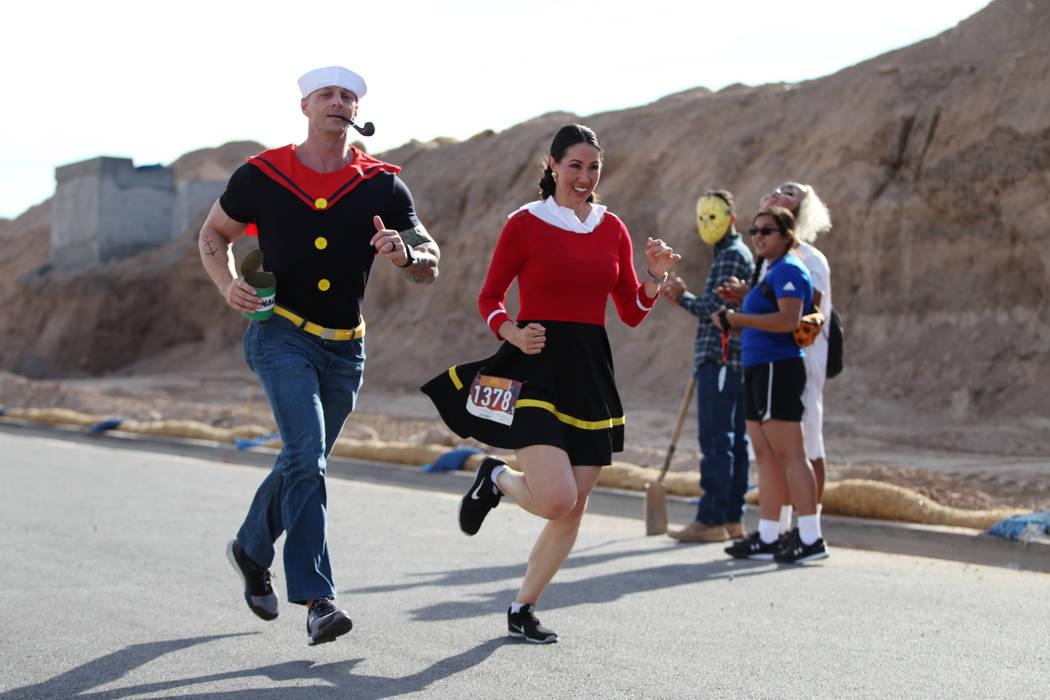 Cory Church, a la izquierda, y su esposa Jennifer de Las Vegas, corren hacia la línea de meta durante la carrera de Halloween 5K en el hotel-casino Fiesta Henderson en Las Vegas, el sábado 27 de ...
