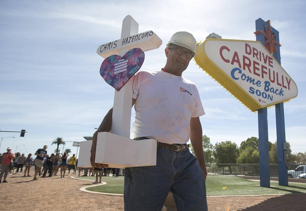Greg Zanis, de Aurora, Illinois, lleva una de las 58 cruces que colocó cerca del cartel de Welcome to Fabulous Las Vegas en honor a las víctimas del tiroteo del 1 de octubre el viernes 28 de sep ...