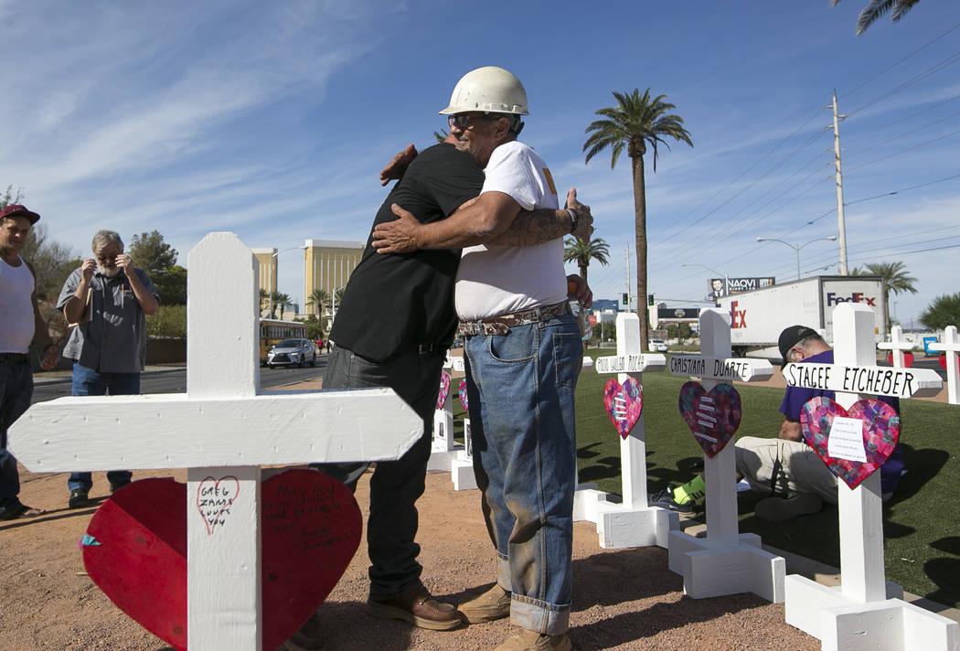 El fabricante de cruces Greg Zanis, a la derecha, recibe un abrazo de parte de Mike Warino, hermano de la víctima del tiroteo del 1 de octubre Heather Alvarado, cerca del cartel Bienvenido a Las ...