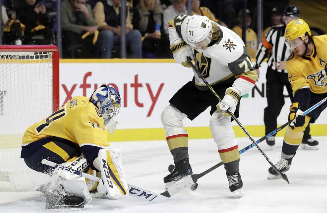 El portero de los Predators de Nashville, Juuse Saros (74), de Finlandia, bloquea el puck frente al centro de los Golden Knights de Las Vegas, William Karlsson (71), de Suecia, en el primer perío ...