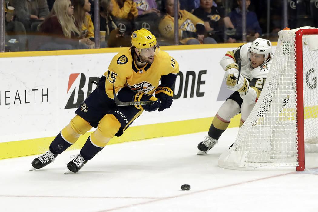 El alero derecho de los Predators de Nashville, Craig Smith (15), juega contra el centro Cody Eakin (21) de Vegas Golden Knights en el tercer período de un juego de hockey de la NHL el martes 30 ...