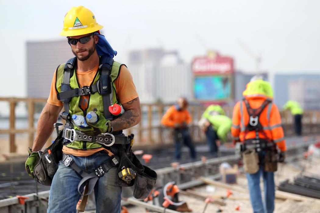 Un trabajador toma botellas de agua mientras trabaja en el Proyecto Neon del Departamento de Transporte de Nevada en la carretera interestatal 15 entre Spaghetti Bowl y Sahara Avenue el jueves 2 d ...