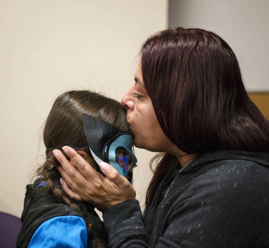 Dawn Hentzi besa a la nueva miembro de su familia recién adoptada, Ammerah de 6 años de edad, luego de jurar en la Corte de Distrito Familiar en Las Vegas, miércoles 31 de octubre de 2018. Caro ...