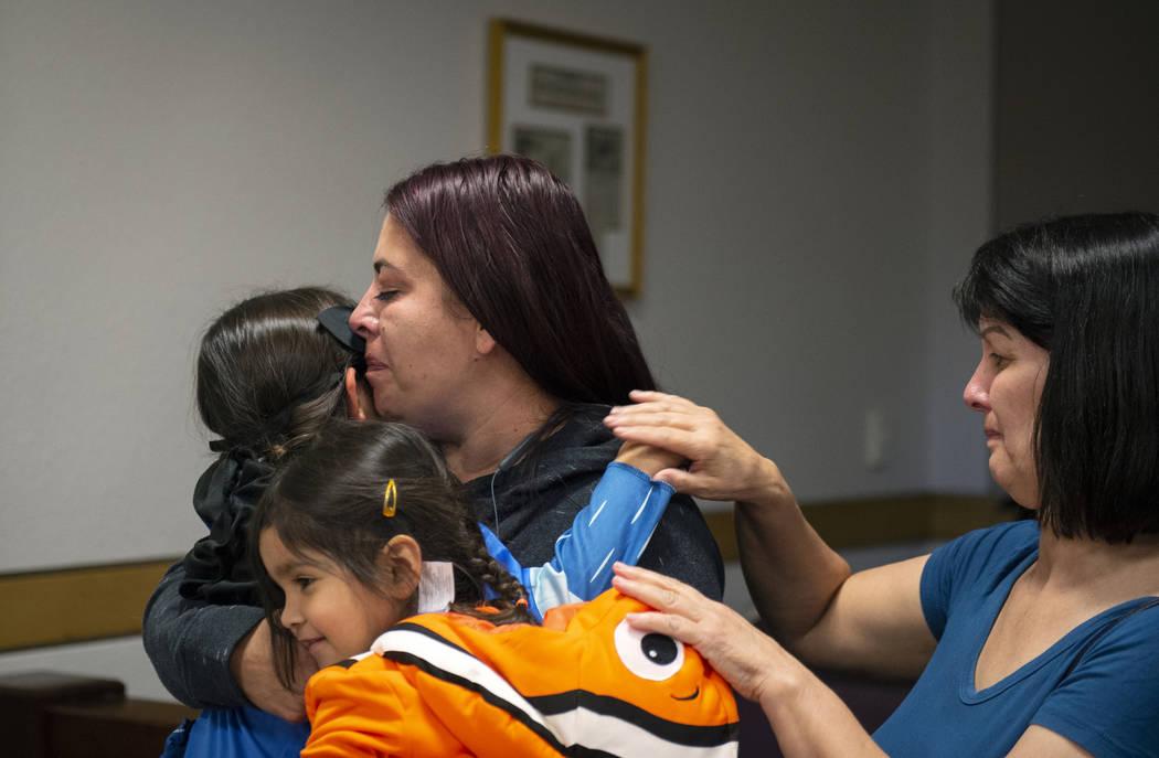 Dawn Hentzi sostiene a su nueva miembro de familia, Ammerah de 6 años, mientras está de pie junto a su otra hija, Elia Raymond, de 3, y su amiga Patty Celis cuando juran ante la Jueza de Familia ...