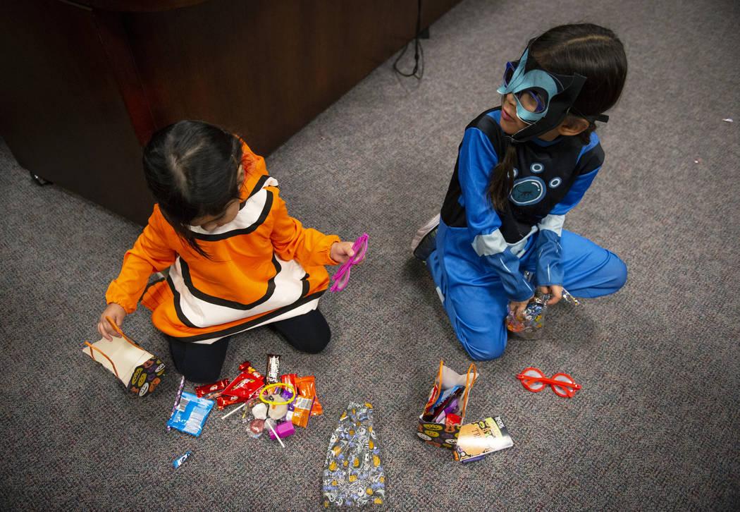 Elia Raymond, de 3 años, mira los dulces que le entregó la Jueza de Familia del Tribunal de Distrito, Cynthia Giuliani, junto a su nueva miembro de la familia, Ammerah de 6 años, en el Tribunal ...