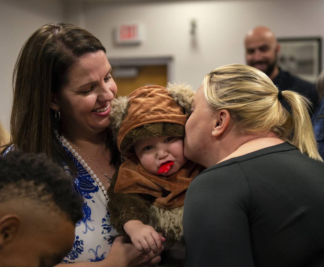 Julie Elliott sostiene a su nuevo miembro de familia, Connor, de un año, mientras Kim Forgione lo besa después de haber jurado ante la Jueza de Familia del Tribunal de Distrito, Cynthia Giuliani ...